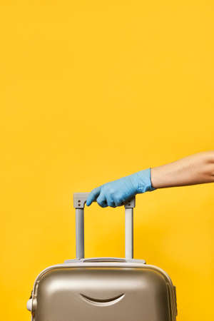 traveling during   pandemic. Borders re-open. Start of traveling. A person in protective medical gloves holding a traveling suitcase over bright yellow background