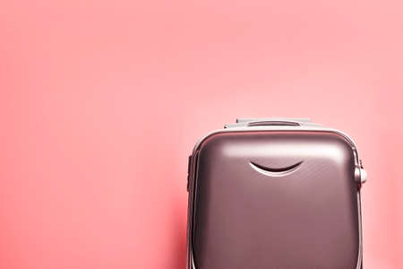 Travel bag on pink background with copy space