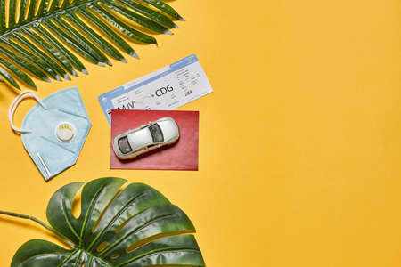 Traveling by car - face mask, toy automobile model and ferry tickets on yellow background 免版税图像