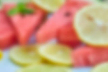 Blurred shot of fresh summer fruits background. Sweet watermelon and lemon slices. Watermelon fruit. Summer fruits background with gaussian blur effect 免版税图像