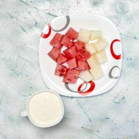 Fresh summer fruits background. A plate of sweet watermelon and melon slices for a light snack