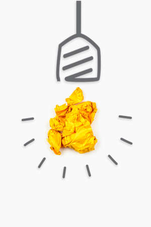 New idea concept. A yellow crumpled paper ball and bulb drawn around it, a symbol of a generating new creative idea