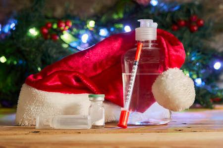Christmas holidays. Antiseptic hand sanitizer bottle, syringe and medicines on wood. Santa cap, coronavirus vaccines and syringe over Xmas tree