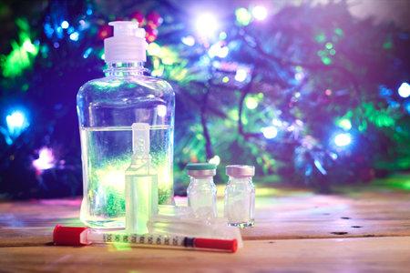 Christmas holidays. Antiseptic hand sanitizer bottle, syringe and medicines on wood. vaccines and syringe over Xmas tree Standard-Bild