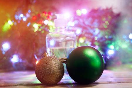 Christmas holidays. Antiseptic hand sanitizing gel over decorated with lights Christmas tree background Standard-Bild
