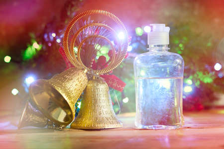 Christmas holidays. Antiseptic hand sanitizing gel and Xmas golden bells over decorated with lights Christmas tree background