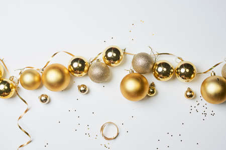 Pile of golden Christmas decorations on white background. Top view of various Xmas festive baubles on white Standard-Bild