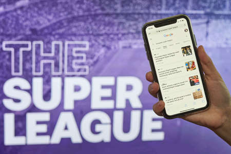 Tashkent, Uzbekistan - April 27, 2021: Hand holding a smartphone with news website over The super league logo. Annual club football competition that would be contested by twenty European football club Editorial
