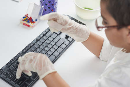 Little schoolboy in protective gloves doing homework on pc