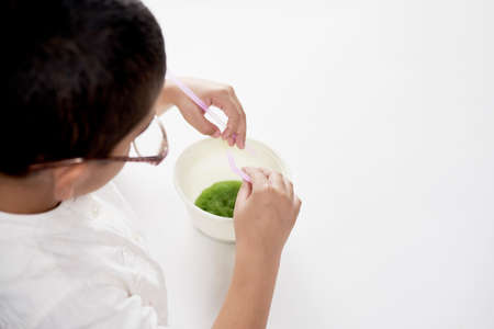 Overhead view of a a little kid experimenting with liquids at home