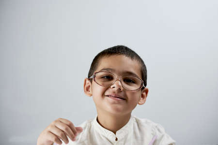 Portrait of cheerful 7 years old mixed race boy against the white background. A smart schoolboy portrait