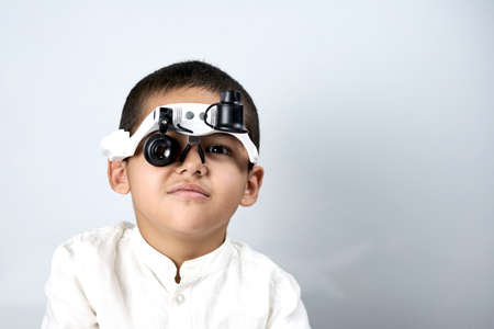 Little boy looking through special magnifying eyeglasses Standard-Bild
