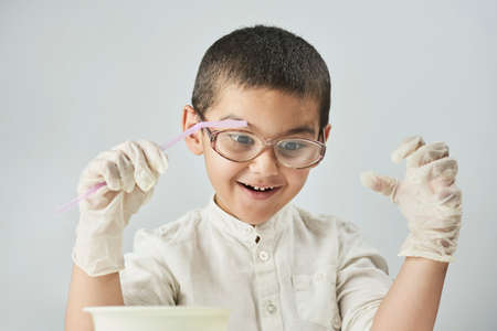 Funny kid making experiments at the workshop and exploring the world of chemistry against the white background