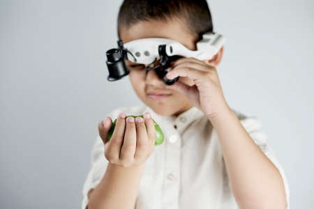 Little boy holding a slime and looking on it through the special magnifying eyeglasses headset Standard-Bild