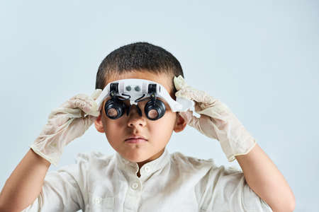 A multiethnic boy in magnifying eyeglasses against the white table