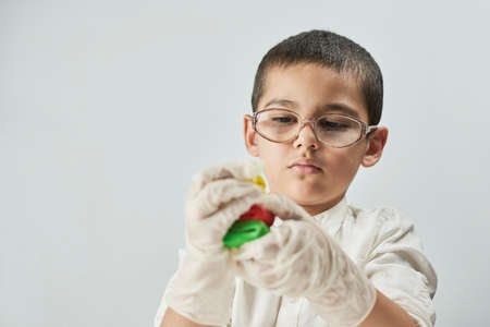 Little boy scientist in white making experiments against the white background