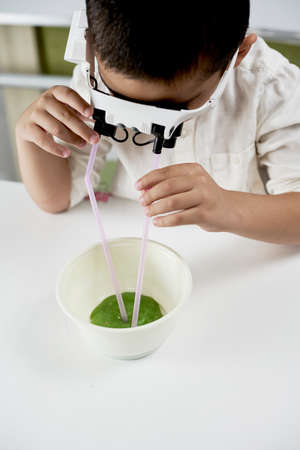 Cute Boy in headband magnifying glass playing with slime