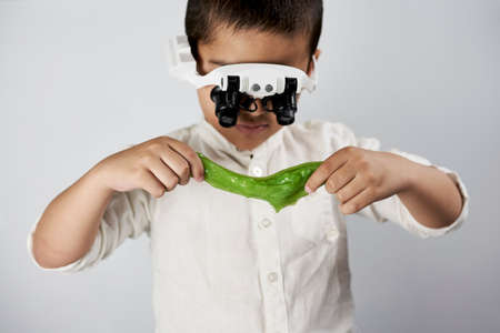 Schoolboy equipped with headband magnifying glass conducting scientific experiments at the workshop