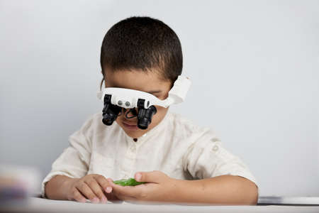 A little smart boy discovering the micro world with headband magnifying glass Standard-Bild