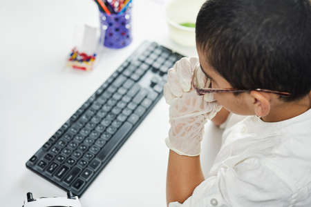 Rearview of a child sitting on the table and doing homework