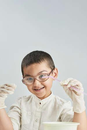Vertical portrait of a happy schoolboy having fun with at classroom Standard-Bild