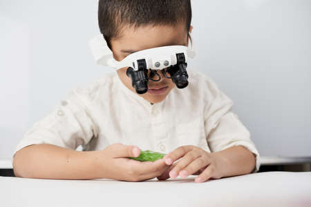 A little boy exploring slime structure with head magnifying glasses headset Standard-Bild