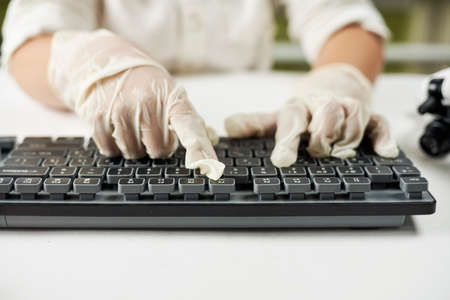 Close up shot of hands of a young child in protective gloves typing on pc keyboard
