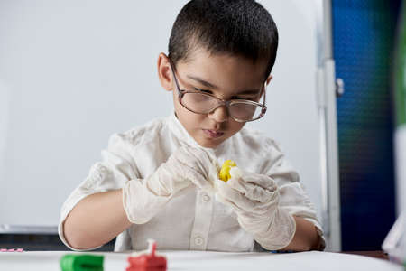 A portrait of cute boy in protective gloves and glasses making plasticine figures on the table Standard-Bild