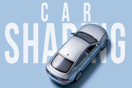 Car sharing concept with gray car toy on blue background