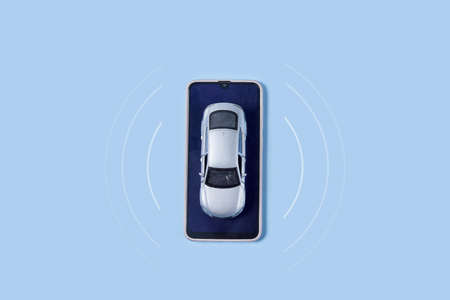 Car toy and mobile phone on blue background. Automobile with gps tracking pulsing signal. A vehicle transmitting gps signal. Searching car location with gps tracker and smartphone Standard-Bild