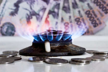 Burning gas stove burner and Uzbek money - sum banknotes. Pay for natural gas, bill, tariff. Growing tariffs for gas. Pile of coins and burning fire gas stove hob and money