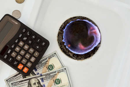 Burning gas stove burner, calculator and US dollar banknotes. Pay for natural gas, bill, tariff. Pile of coins and burning fire gas stove hob and money. Calculating gas tariff or cost