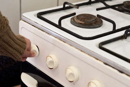Woman checking gas. Female hand trying to turn on old gas stove. No gas, Winter and cold period concepts. Lack of gas in the pipeline