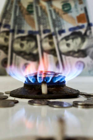 Burning gas stove burner and US dollar banknotes. Pay for natural gas, gas bill, tariff. Pile of coins and burning fire gas stove hob and money