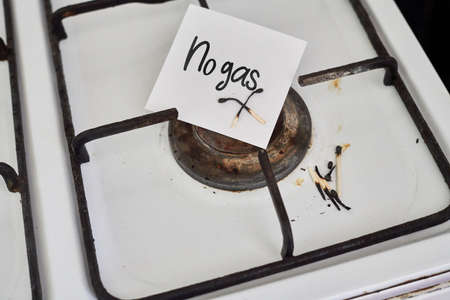 An old and grungy gas stove with no gas and piece of paper with text - No gas Standard-Bild