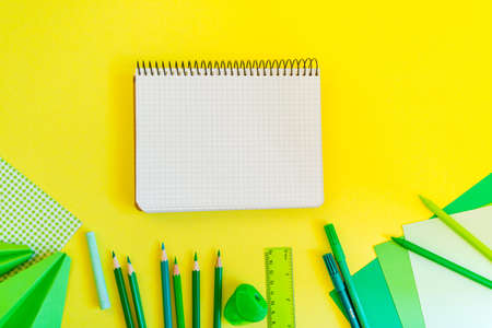 Creative, Fashionable, Minimalistic, School Or Office Workspace With Green  Supplies On Yellow Background