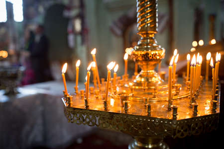 Church candles on the background of icons. Orthodox Church and the interior, a cross and candles during worship