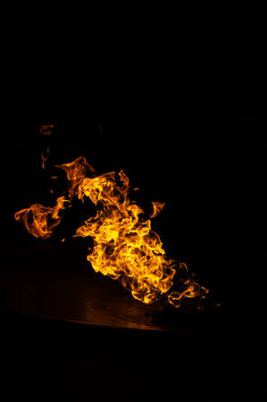 Bright flame in a metal bowl on a black background