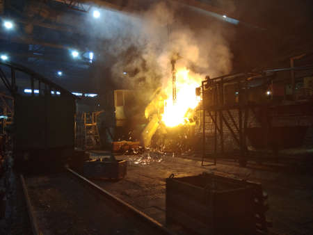 in a foundry, molten metal is poured from a furnace into a ladle Фото со стока