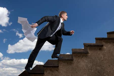 doelen: Een jonge man streven op de ladder met de uitgezonden vellen papier