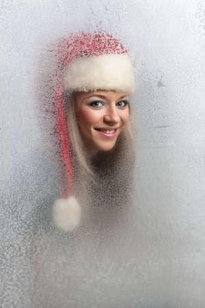 beautiful girl in a frozen glass, in red cap