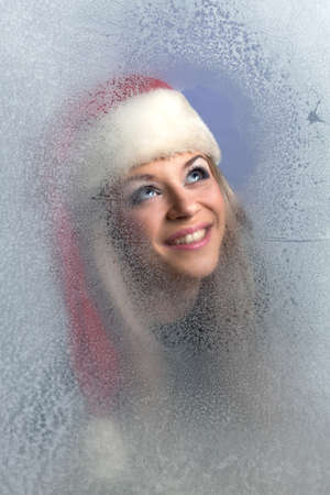 beautiful girl in a frozen glass in the red cap looks up