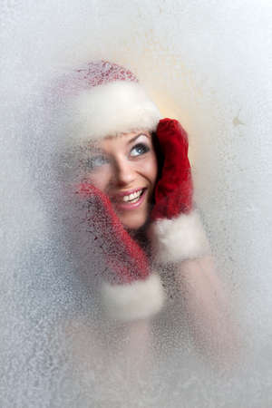 beautiful girl in a frozen glass in a red hat and red mittens Stock Photo