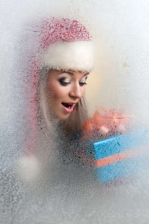 beautiful girl in a frozen glass in a red cap with a gift in hand Stock Photo