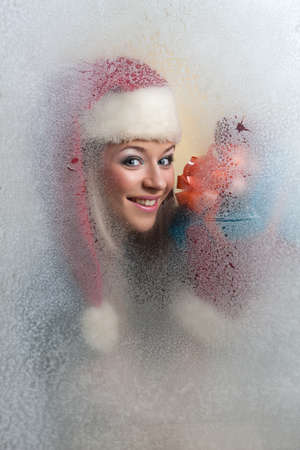 beautiful girl in a frozen glass in a red cap with a gift in his hands looking at camera Stock Photo