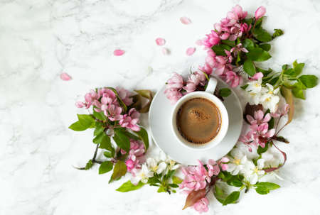 Coffee on the marble table. Apple tree flowers on a spring day. Women's desktop