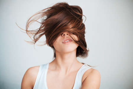 beauty shot: The womans face half closed by hair.