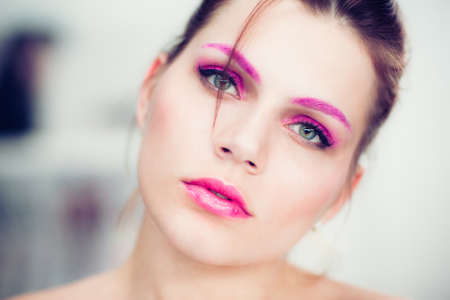 The woman with a bright pink make-up. Studio portrait. photo