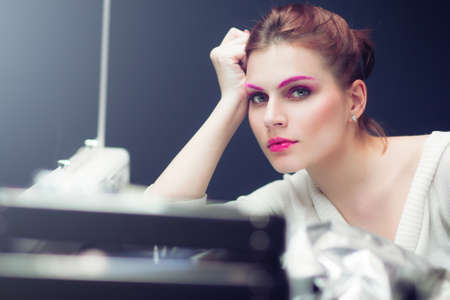 The woman with a bright pink make-up attentively looks forward. Studio portrait. photo