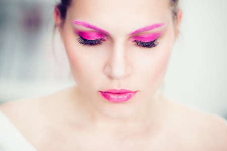 The woman with a bright pink make-up, pink eyebrows and false eyelashes. Studio portrait. photo